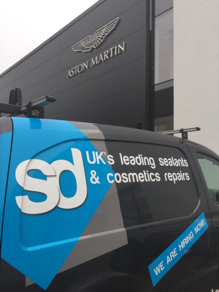 sd van outside the aston martin garage